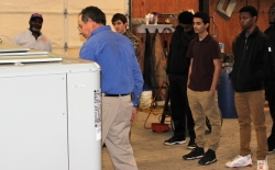 Owner of Advance Mechanical explaining package HVAC unit to students at community college