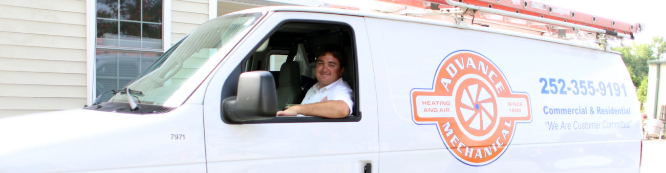 man smiling and looking out the window of the Advance Mechanical service van