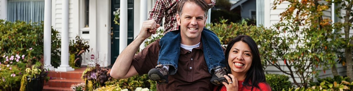 woman in red shirt and man with brown shirt and child on his shoulders smile in front of house