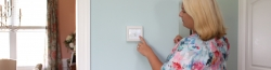 woman turning thermostat down
