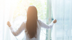 woman with long dark hair looking out of window